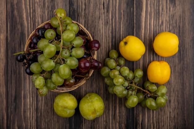 Vue de dessus des fruits comme des raisins dans le panier et des nectacots verts pluots sur fond de bois