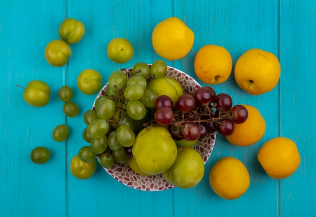 Vue de dessus des fruits comme des raisins verts pluots dans un bol et motif de prunes et nectacots sur fond bleu