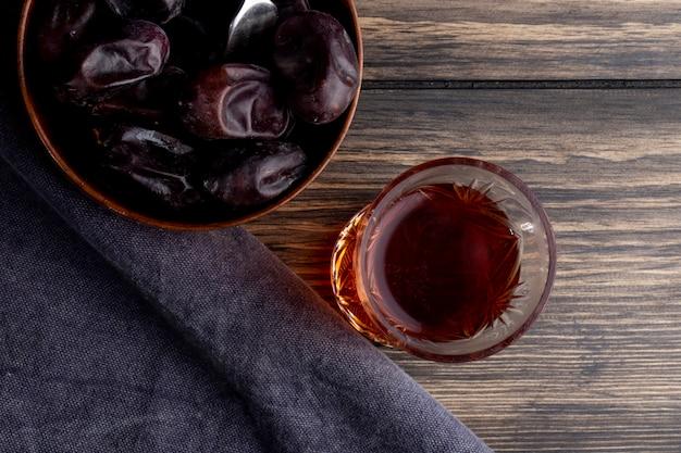 Vue de dessus des fruits de datte séchés sucrés dans un bol avec un verre de thé armudu sur bois