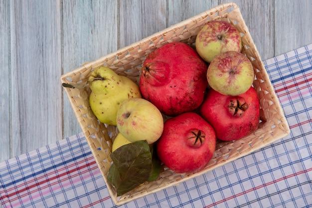 Vue de dessus des fruits frais comme les pommes grenades et les coings sur un seau sur un tissu vérifié sur fond gris