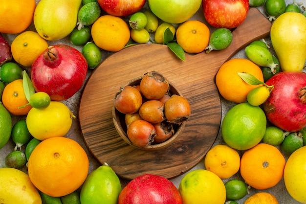 Vue de dessus des fruits frais différents fruits mûrs et moelleux sur fond blanc couleur berry photo santé régime savoureux