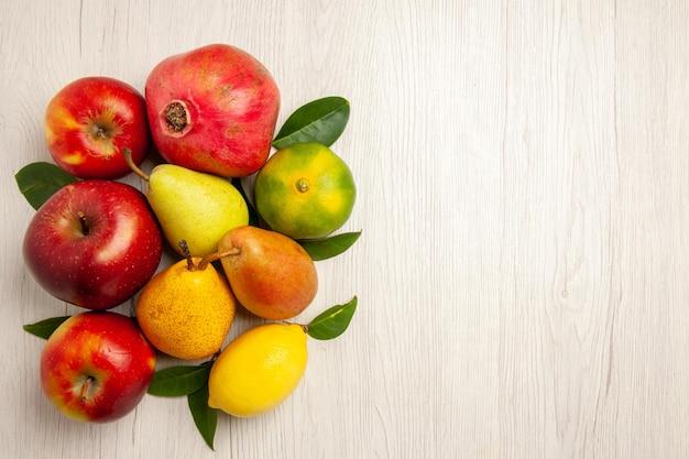 Vue de dessus fruits frais pommes poires et autres fruits sur un bureau blanc fruits mûrs couleur des arbres moelleux beaucoup de frais