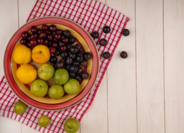 Vue de dessus des fruits frais tels que les cerises rouges, les prunes et les pêches cerises vertes sur un bol sur un tissu vérifié sur un fond en bois blanc avec espace de copie