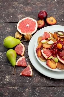 Vue de dessus des fruits frais tranchés mûrs et moelleux à l'intérieur de la plaque blanche