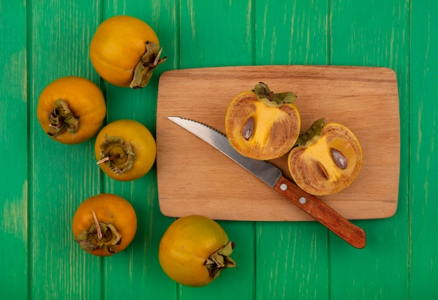 Vue de dessus des fruits de kaki arrondis orange sur une planche de cuisine en bois avec un couteau sur une table en bois vert