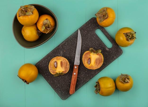 Vue de dessus des fruits de kaki arrondis orange sur une planche de cuisine noire avec un couteau avec des fruits de kaki sur un bol sur une table en bois bleu