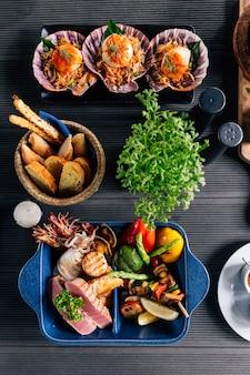 Vue de dessus de fruits de mer mélangés grillés tels que poissons, calmars, crevettes roses, moules et légumes.