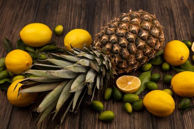 Vue de dessus de fruits sains tels que les citrons d'ananas et les kinkans isolés sur un fond en bois