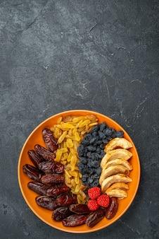 Vue de dessus des fruits secs avec des raisins secs à l'intérieur de la plaque sur un bureau gris