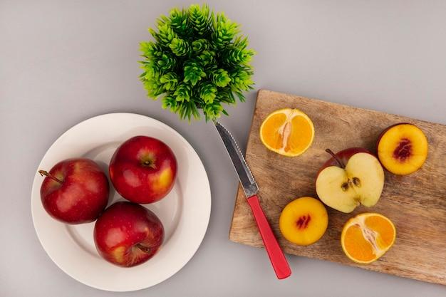 Vue de dessus des fruits sucrés tels que les pêches, les pommes et les mandarines isolés sur une planche de cuisine en bois avec un couteau avec des pommes rouges sur une assiette sur un mur gris