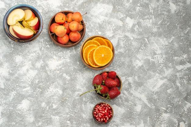 Vue de dessus fruits en tranches pommes et oranges avec des baies sur fond clair fruits frais doux santé vitamine