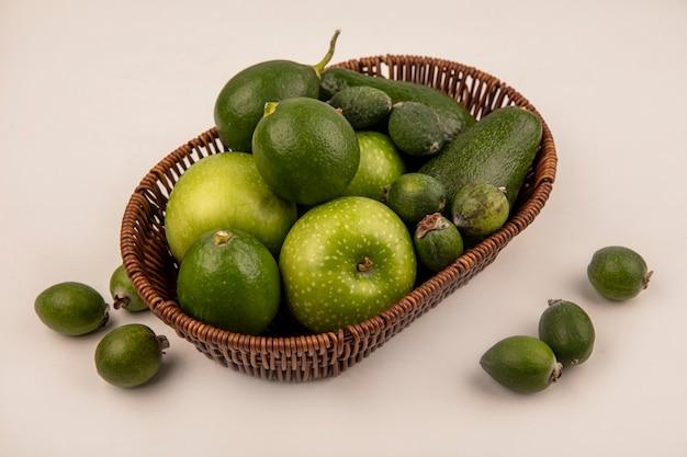 Vue de dessus de fruits verts sains tels que les pommes, les avocats, les limes et les feijoas sur un seau sur un mur blanc