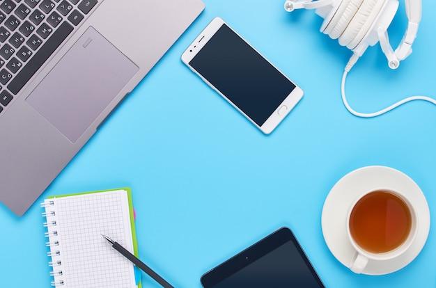Vue de dessus sur les gadgets sur fond bleu, la composition d'un ordinateur portable, un casque blanc, un téléphone, un verre avec une boisson et des clés de voiture