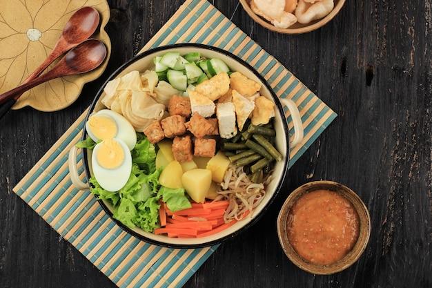 Vue de dessus gado gado salade de mélange indonésienne à partir de légumes bouillis ou à la vapeur, servie avec une sauce aux arachides. gado-gado siram populaire à jakarta à base de pomme de terre, tempeh, tofu, germe, carotte, haricot long et œuf