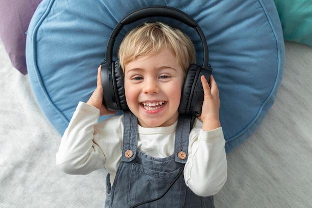 Vue de dessus garçon écoutant de la musique sur des écouteurs