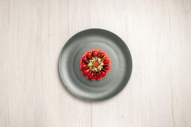 Vue de dessus gâteau au chocolat arrondi avec cornouiller et framboise au centre dans la plaque grise sur le fond en bois blanc