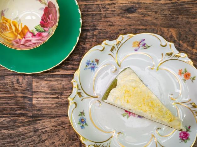 Vue de dessus, gâteau au fromage au thé vert sucré surmonté de chocolat blanc posé sur une assiette blanche.