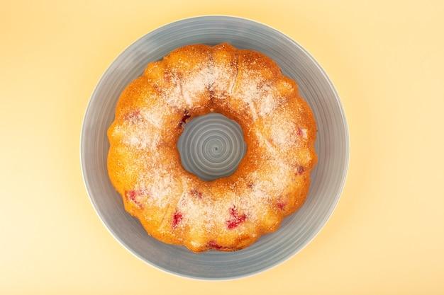 Une vue de dessus gâteau aux cerises rond formé à l'intérieur de la plaque grise sur le bureau jaune gâteau biscuit sucre sucré