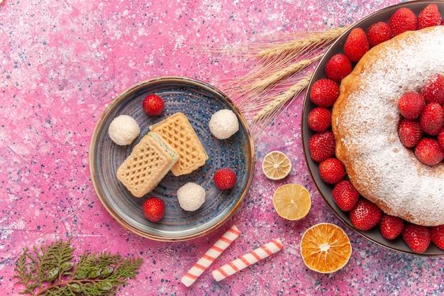 Vue de dessus gâteau aux fraises tarte en poudre de sucre avec des gaufres sur le rose