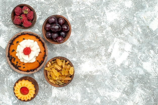Vue de dessus gâteau aux pépites de chocolat avec raisins secs et fruits sur fond blanc tarte biscuit biscuit gâteau sucré
