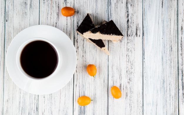 Vue de dessus gâteau croquant à la gaufre sur la gauche avec tasse de café kumquat et espace copie sur fond de bois blanc