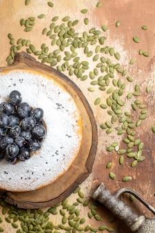 Vue de dessus un gâteau un gâteau aux raisins sur la planche à découper à côté des graines de citrouille