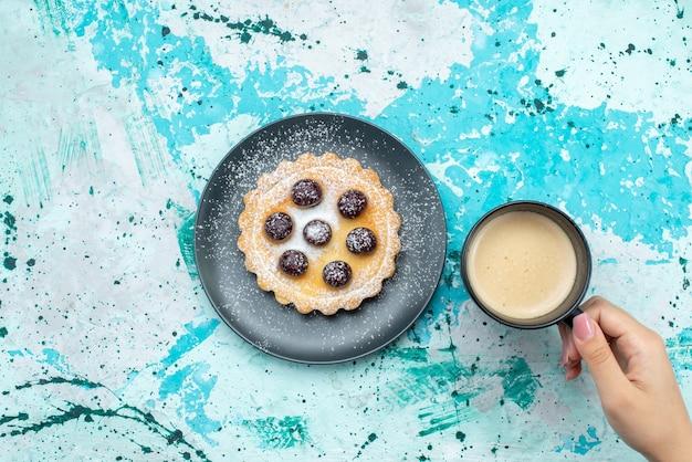 Vue de dessus gâteau en poudre de sucre avec des fruits avec du lait sur le gâteau de bureau bleu couleur biscuit au sucre