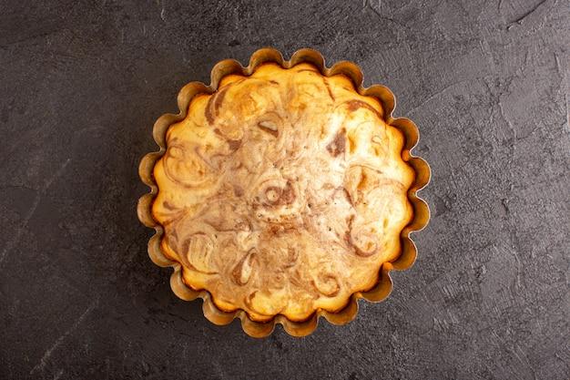 Une vue de dessus gâteau rond sucré délicieux délicieux à l'intérieur du moule à gâteau sur le fond gris biscuit biscuit au sucre