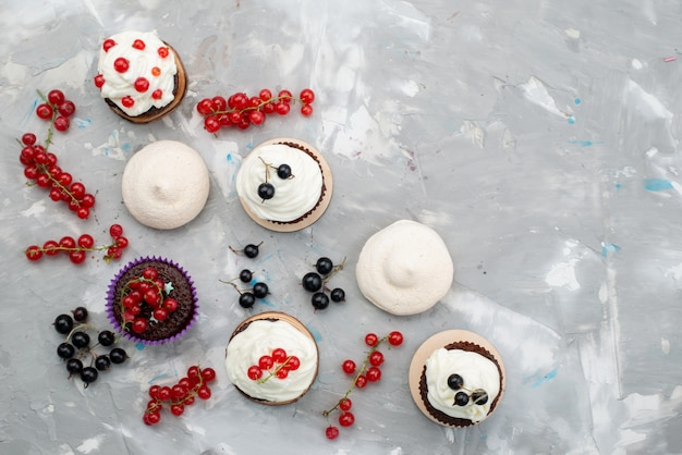 Une vue de dessus des gâteaux au chocolat avec crème beignets conçu avec des fruits sur le fond blanc gâteau biscuit beignet chocolat
