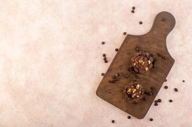 Une vue de dessus des gâteaux au chocolat délicieux et délicieux sur le bureau en bois et table rose