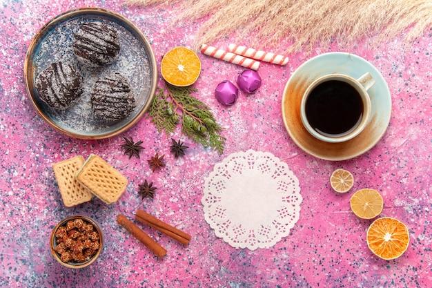 Vue de dessus des gâteaux au chocolat avec des gaufres et une tasse de thé sur un bureau rose
