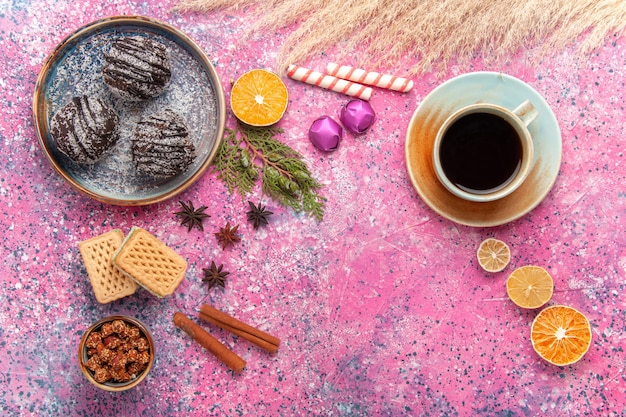 Vue de dessus des gâteaux au chocolat avec des gaufres et une tasse de thé sur rose clair