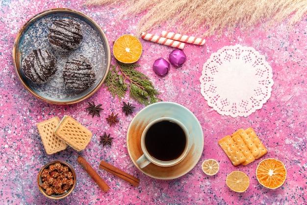 Vue de dessus des gâteaux au chocolat avec des gaufres et une tasse de thé sur rose