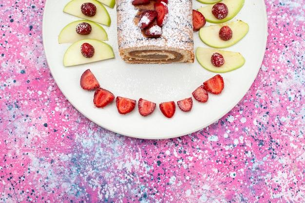 Vue de dessus des gâteaux au chocolat à l'intérieur de la plaque blanche avec des pommes et des fraises sur le fond rose gâteau biscuit sucre sucré