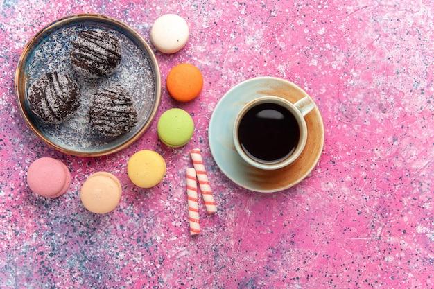 Vue de dessus des gâteaux au chocolat avec des macarons français sur rose
