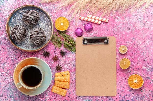 Vue de dessus des gâteaux au chocolat avec une tasse de thé sur rose clair