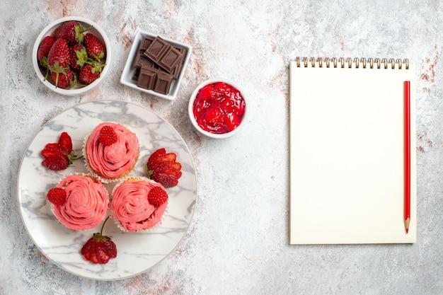 Vue de dessus des gâteaux aux fraises roses avec de la confiture et des barres de chocolat sur une surface blanche