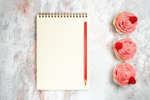 Vue de dessus des gâteaux aux fraises roses avec de la crème et du bloc-notes sur une surface blanche