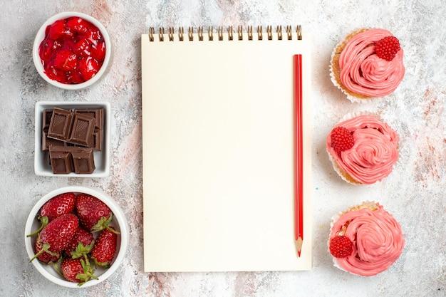 Vue de dessus des gâteaux aux fraises roses avec de la crème sur une surface blanche