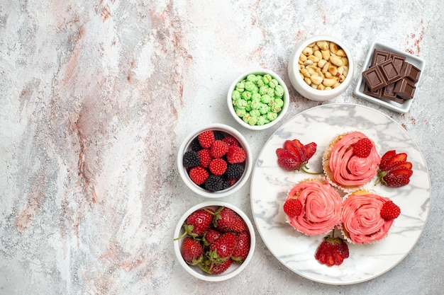 Vue de dessus des gâteaux aux fraises roses avec des noix et des bonbons sur une surface blanche