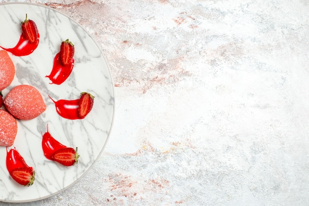 Vue de dessus gâteaux aux fraises roses petits bonbons sur sol blanc gâteau biscuit thé biscuit aux fruits sucre sucré
