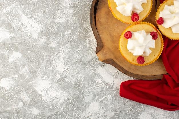 Vue de dessus des gâteaux à la crème cuit au four conçu avec de la framboise sur le fond gris crème biscuit sucrée