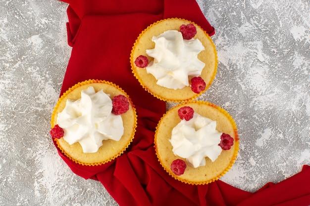 Vue de dessus des gâteaux avec de la crème cuite au four délicieux conçu avec des framboises sur le bureau gris crème sucrée au sucre
