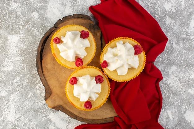 Vue de dessus des gâteaux avec de la crème cuite au four délicieux conçu avec des framboises sur le bureau lumineux crème biscuit sucrée