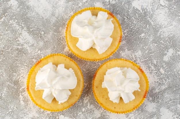 Vue de dessus des gâteaux avec de la crème délicieuse cuite au four sur le fond gris sucre crème biscuit sucré