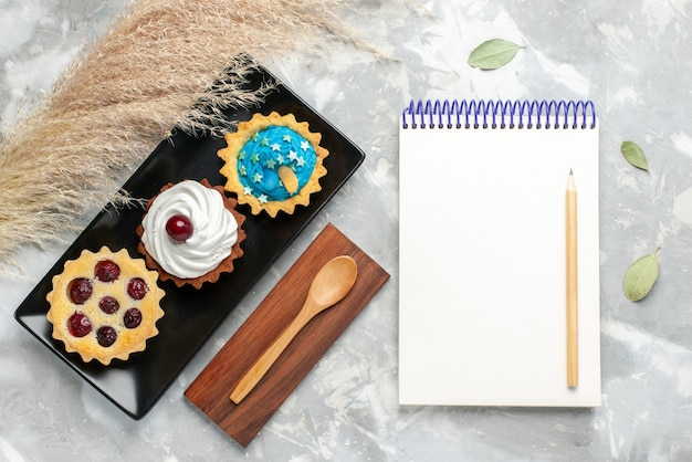Vue de dessus des gâteaux à la crème avec des frutis avec bloc-notes sur bureau gris clair, gâteau biscuit sucre sucré