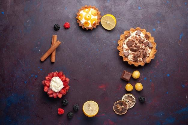 Vue de dessus des gâteaux crémeux avec des fruits et des confitures de baies sur la surface sombre