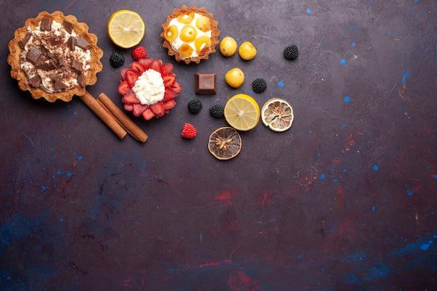 Vue de dessus des gâteaux crémeux avec des fruits et des confitures de baies sur une surface violet foncé