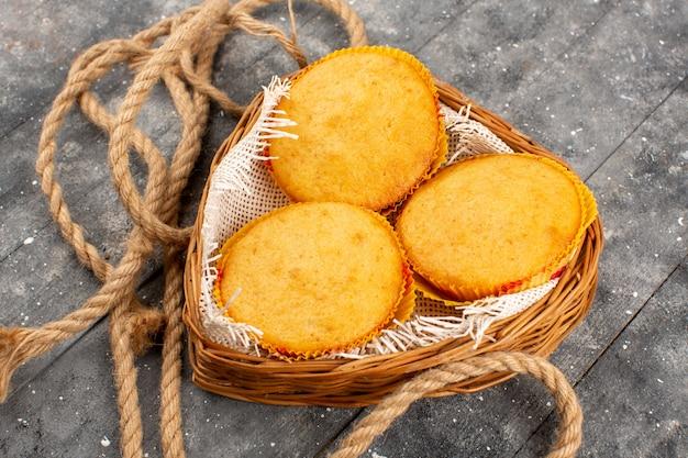 Vue de dessus gâteaux délicieux délicieux rond doux à l'intérieur du panier sur le bois rustique gris