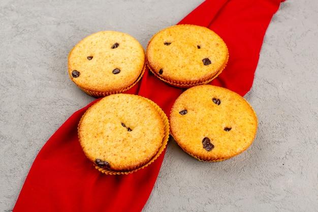 Vue de dessus des gâteaux délicieux sucrés sur le tissu rouge et le bureau gris